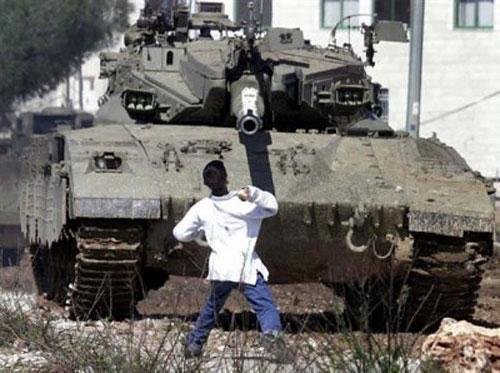 Le garçon Palestinien Faris Odeh (qui a ensuite été tué par les forces d'occupation) jette une pierre sur un blindé israélien pendant la 2e intifada (Source: flickr)